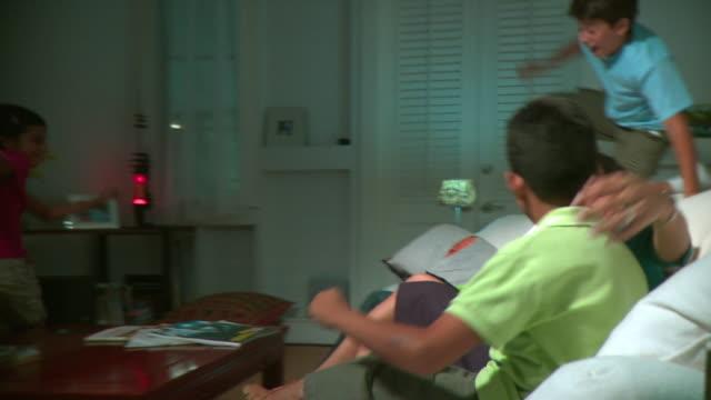 stockvideo's en b-roll-footage met ms pan three children (7-12) joining parents watching tv, panama city, panama  - 12 13 jaar