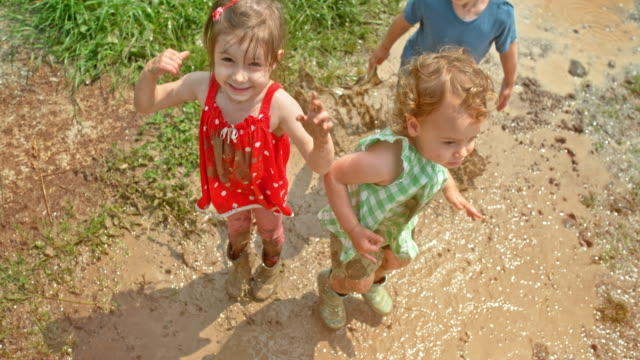 slo mo three children jumping up and down in the muddy puddle in sunshine - mud stock videos & royalty-free footage