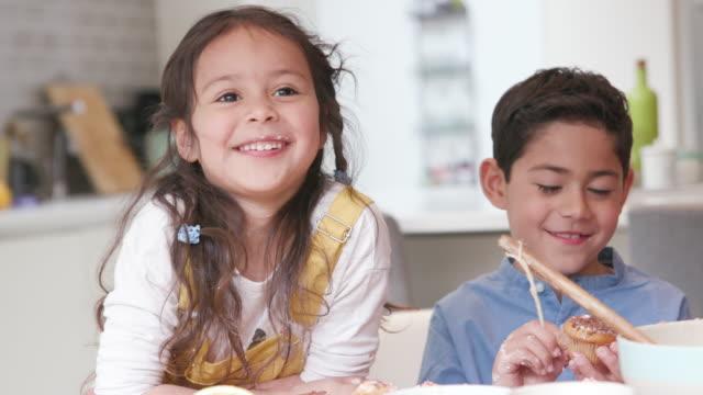 vídeos de stock, filmes e b-roll de três crianças que fazem e que comem bolos junto na cozinha - irmão