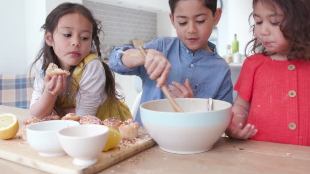 three children making cakes together at home in the kitchen - messy stock videos & royalty-free footage