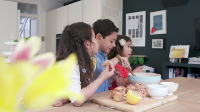 drei kinder backen gemeinsam kuchen in der küche - messy stock-videos und b-roll-filmmaterial