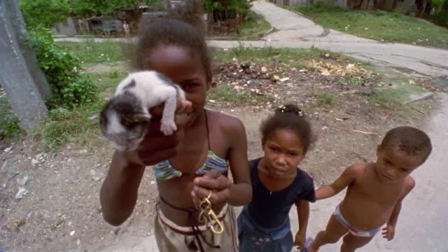 CU, Three children (4-5, 12-13, 13-14) outdoors, girl holding kitten, Santiago de Cuba, Cuba