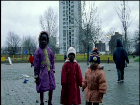 Three children outdoors in winter clothes one runs to camera