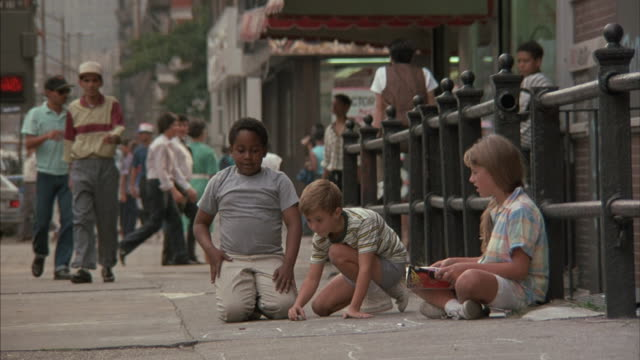 three children play on a sidewalk in new york city. - child sitting cross legged stock videos & royalty-free footage