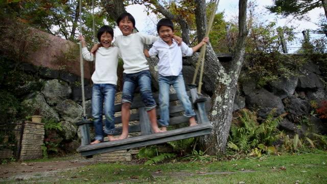 vídeos y material grabado en eventos de stock de ms three children play sitting on swing / fujikawaguchiko, yamanashi, japan - columpiarse