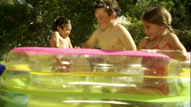 CU, Three children (6-7) playing in inflatable pool in garden