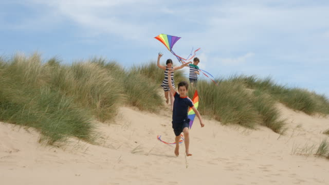 three children running through sand dunes flying their kites at the beach. - kid with kite stock videos & royalty-free footage