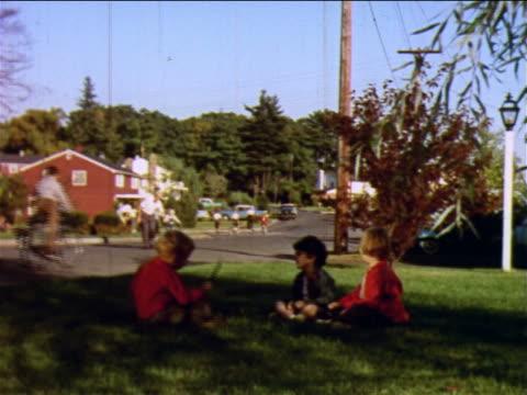 1957 three children sitting in grass in yard / children riding bicycles in street in background / NJ