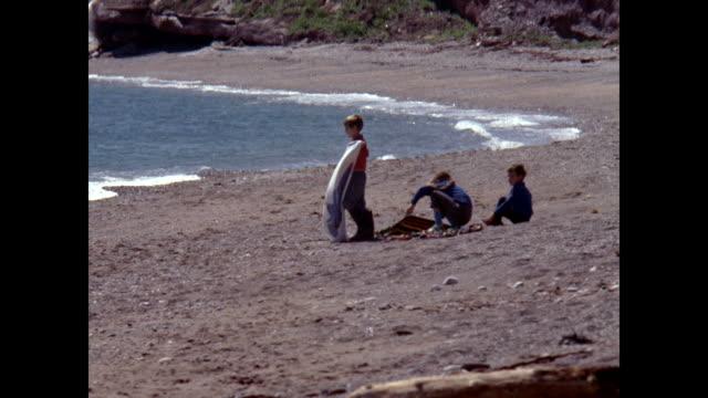 stockvideo's en b-roll-footage met three children sitting on beach trying to spread blanket against the wind - noord atlantische oceaan