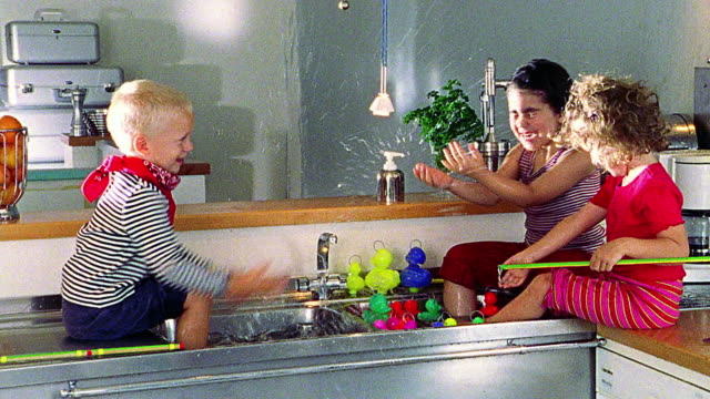 three children splashing each other in sink - unfug stock-videos und b-roll-filmmaterial