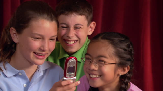 three children text messaging on cell phone / los angeles, california - 男性と複数の女性点の映像素材/bロール