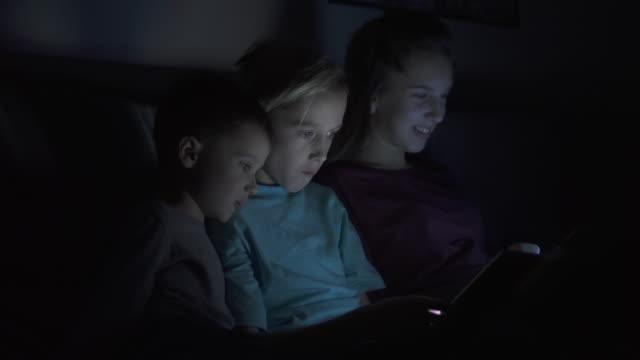 Three children using digital tablet at night