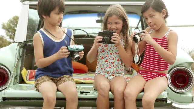 three children with cameras - 撮影テーマ点の映像素材/bロール