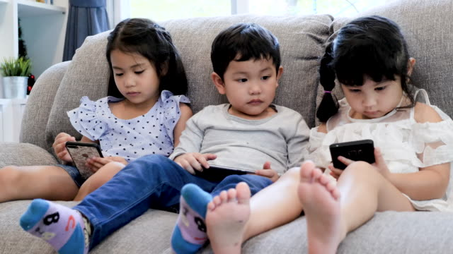three childs using digital devices on sofa at home - electronic book stock videos & royalty-free footage