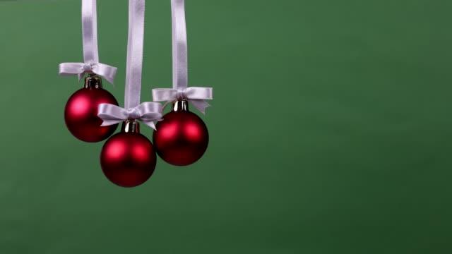 stockvideo's en b-roll-footage met drie kerst decoratie ballen vallen één voor één - kerstversiering