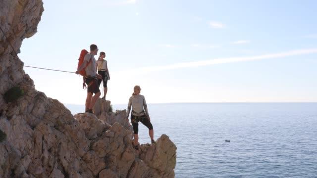 three climbers pause on rock climb, above sea - three people stock videos & royalty-free footage