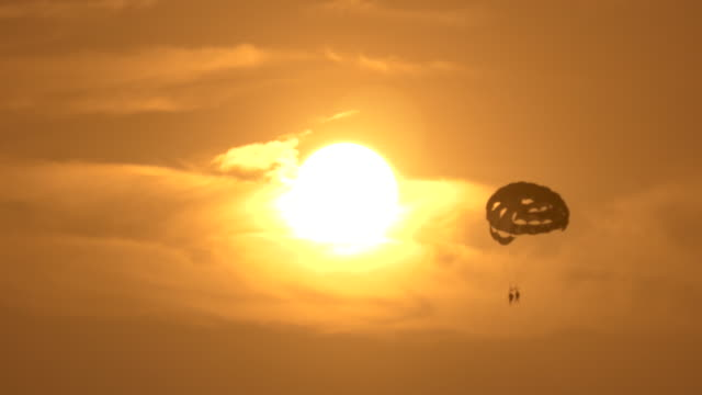 three clips of a paraglider on a sunny day at the beach, flying high above the water - santa monica stock videos & royalty-free footage