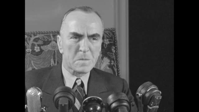 three close ups of eddie rickenbacker wwi fighter ace and medal of honor winner sitting at desk preparing to speak several microphones sit on desk in... - エディ リッケンバッカー点の映像素材/bロール