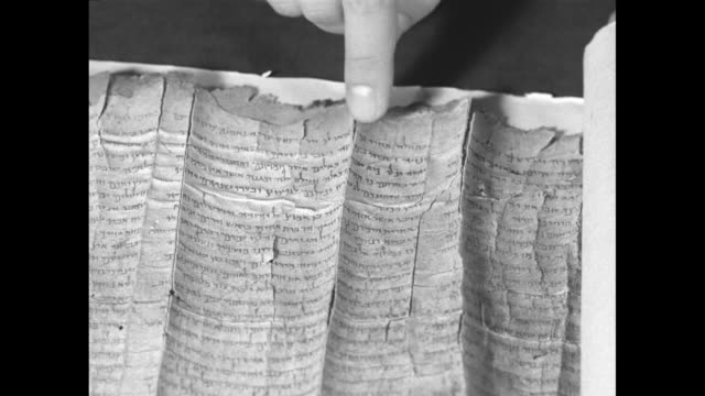 "three close ups of hands of mar samuel metropolitan of jerusalem of the syrian orthodox church unrolling scroll and his finger pointing to writing in... - newsreel ""dead sea scrolls video stock e b–roll"