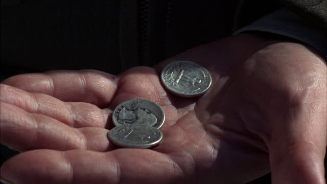 CU Three coins in mans hand / Los Angeles, California, United States
