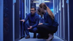 Three colleagues crouching by the server in the server room and troubleshooting
