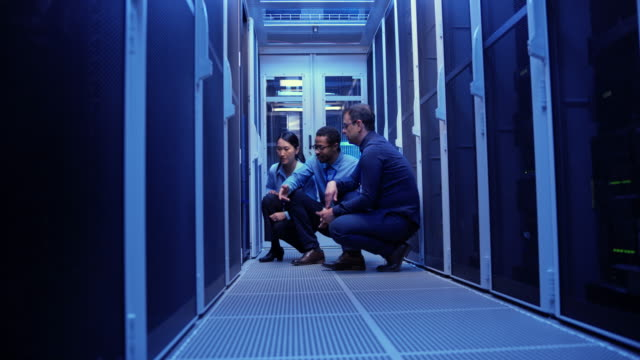 three colleagues crouching by the servers in the server room and checking for a solution - server room stock videos & royalty-free footage