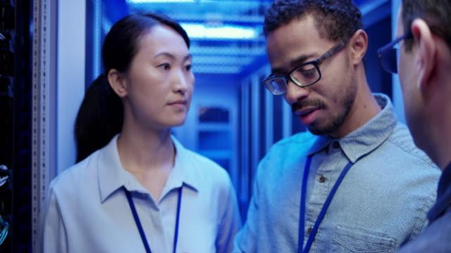 サーバー ルームのサーバー操作を議論する 3 人の同僚 - 集中点の映像素材/bロール