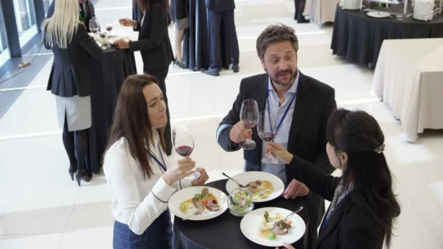three colleagues eating lunch with a glass of wine during a seminar break in the conference center - attending stock videos & royalty-free footage