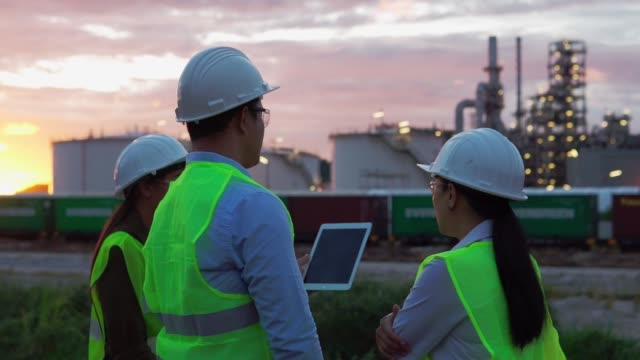 three colleagues of engineers a man and a woman discussing a tablet computer on the industrial, oil or gas plant background - chemical stock videos & royalty-free footage