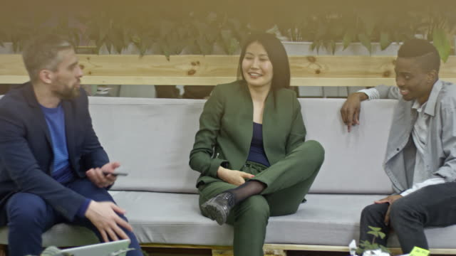 Three colleagues sitting on couch and talking