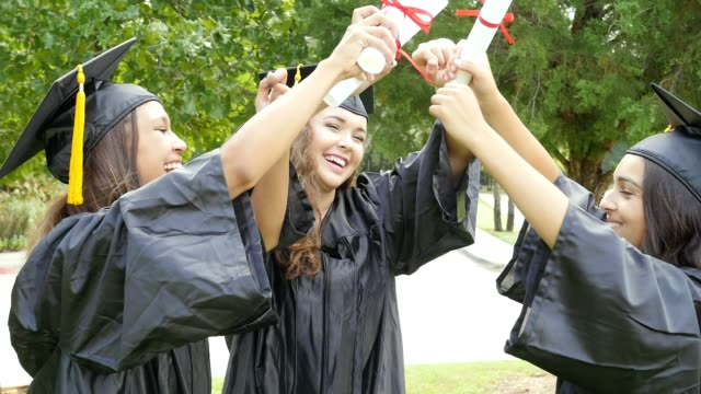 Three college friends celebrate after graduation