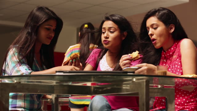 vídeos de stock e filmes b-roll de three college students eating food in the college - cantina