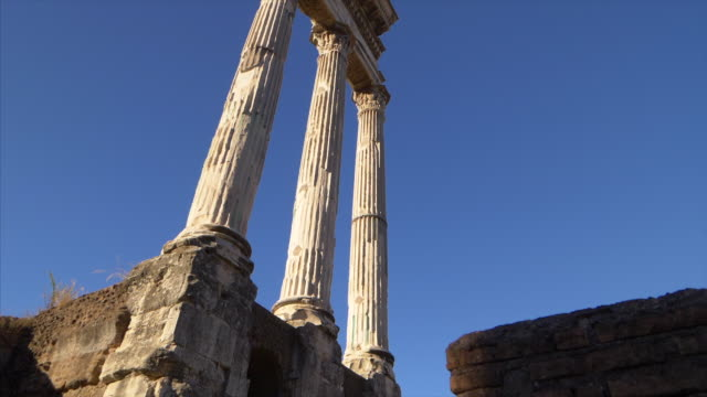 Three columns of the Temple of Castor and Pollux at the Roman Forum in Rome, Italy (slow motion tilt)