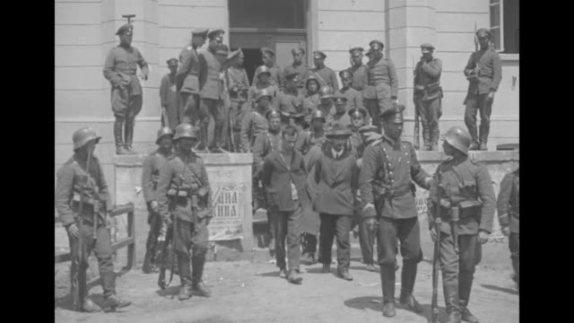 vidéos et rushes de three communists with their hands bound leave a courthouse watched over by bulgarian soldiers / king boris iii salutes while walking past civilians;... - communisme