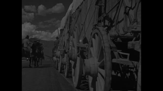 vídeos de stock, filmes e b-roll de three conestoga wagons move on idaho plain being pulled by team of mules escorted by horses and riders / side views of wagons and turning wheels /... - veículo puxado a cavalo