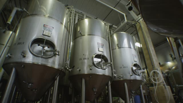 three conical brewing vats stand together in a factory. - 醸造所点の映像素材/bロール