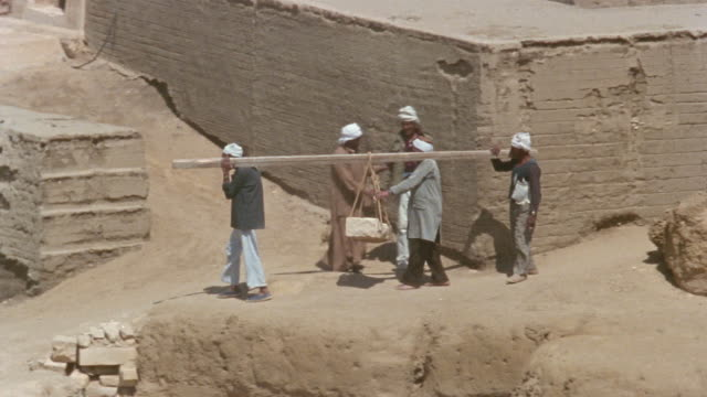 ha ws pan three construction workers carrying large stone to the foot of the sphinx during renovations/ giza, egypt - stone material stock videos and b-roll footage