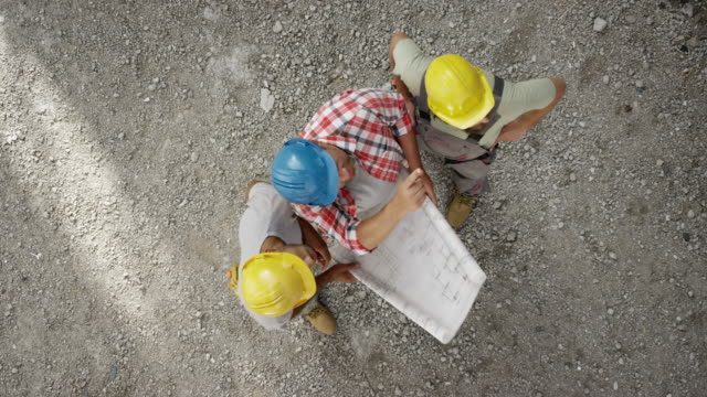ld three construction workers checking the plans at the construction site - construction worker stock videos & royalty-free footage