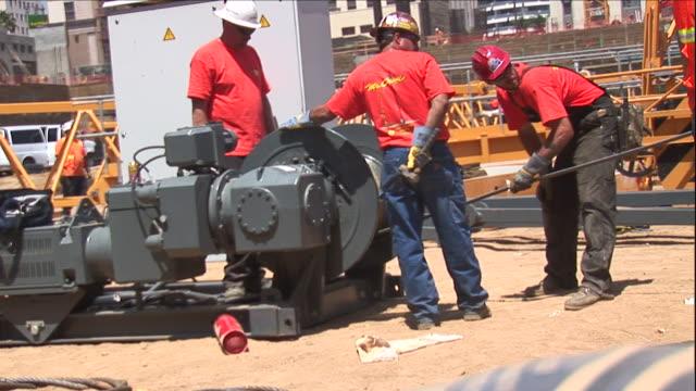 vídeos y material grabado en eventos de stock de three construction workers guide a cable onto a spool at a construction site. - bobina