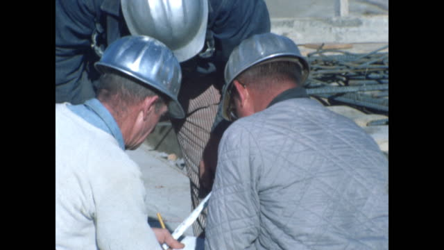 three construction workers in hard hats looking at drawing - tape measure stock videos & royalty-free footage
