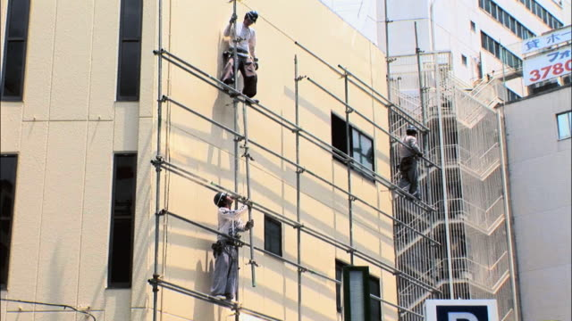 la ws three construction workers standing on scaffold / tokyo, japan - 建設作業員点の映像素材/bロール