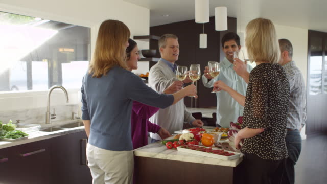 ms three couples standing in kitchen of contemporary home toasting wine glasses before dinner - einen toast ausbringen stock-videos und b-roll-filmmaterial