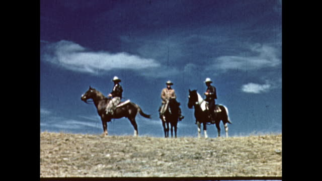 three cowboys on a hill in the blue sky. - カウボーイ点の映像素材/bロール