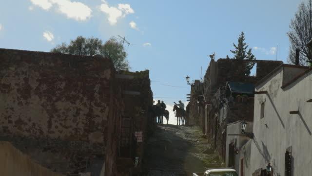 WS Three cowboys on horseback on cobblestone street / Real de Catorce, San Luis Potosi, Mexico