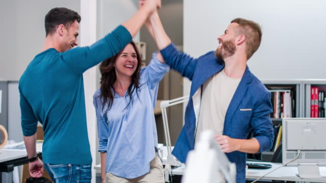 three creative business colleagues giving high-five - femmina con gruppo di maschi video stock e b–roll