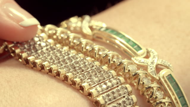 cu three diamond studded bracelets on female arm as hand pulls one bracelet across /  los angeles, california, usa  - luxus stock-videos und b-roll-filmmaterial