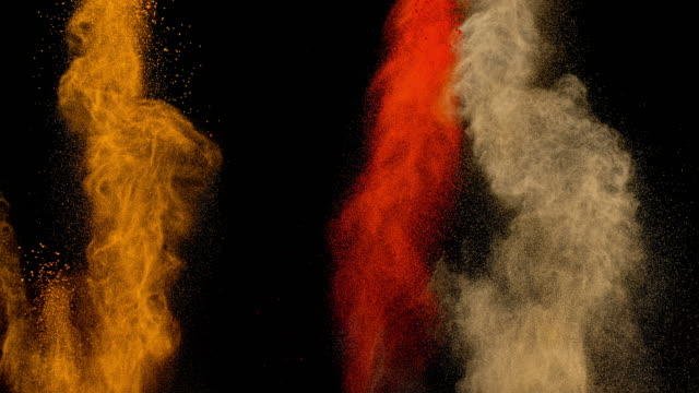 slo mo ld three different powdered spices exploding against black background - spice stock videos & royalty-free footage