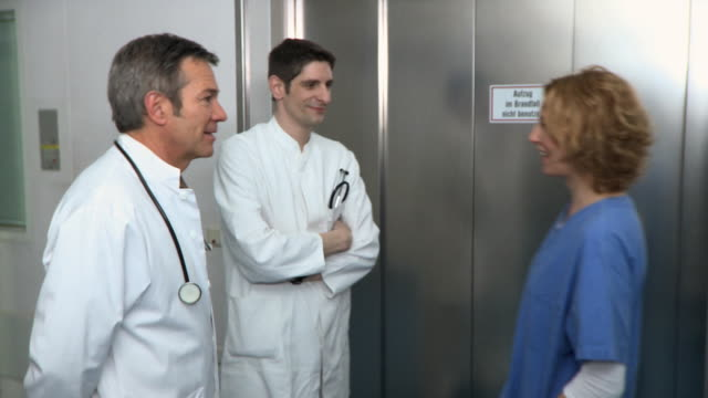 ms, three doctors entering elevator in hospital, berlin, germany - tre quarti video stock e b–roll