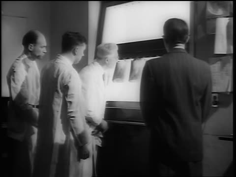 b/w 1948 three doctors examining + discussing x-rays with man in suit - black and white stock videos & royalty-free footage
