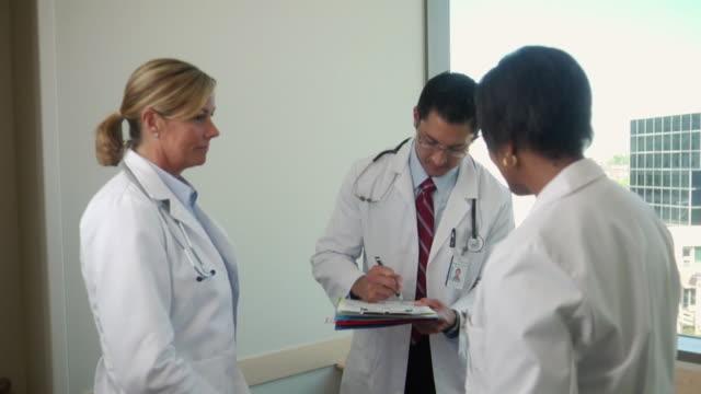 stockvideo's en b-roll-footage met ms three doctors signing patient's chart and shaking hands, seattle, washington, usa - man met een groep vrouwen